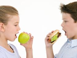 Zwei Schüler stehen sich gegenüber, das Mädchen beisst in einen Apfel, der Junge in einen Burger